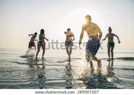 Group of happy friends running in to water at sunset - Silhouettes of active people having fun on the beach on vacation - Tourists going to swim on a tropical island
