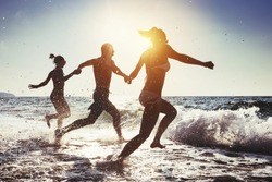 Group of happy friends runs to the sea. Tropical beach at sunny evening