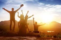 Group of happy friends sits with raised hands on background of sunset or sunrise bay with islands. Space for text