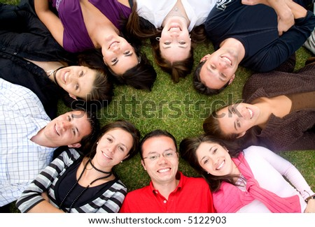 group of happy friends smiling with heads together on the floor