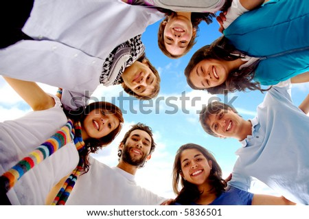 group of happy friends smiling with heads together outdoors with a blue sky in the background