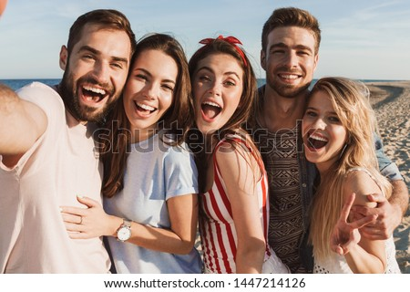 Group of happy friends spending time together at the beach, taking a selfie
