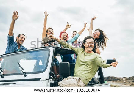 Photo of  Group of happy friends taking selfie with mobile smart phone on jeep car - Young people having fun making photo during their road trip - Friendship, vacation, youth holidays lifestyle concept