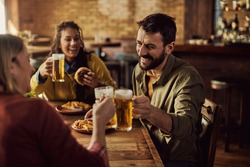 Group of happy friends toasting with beer while having lunch in a pub. Focus is on man.