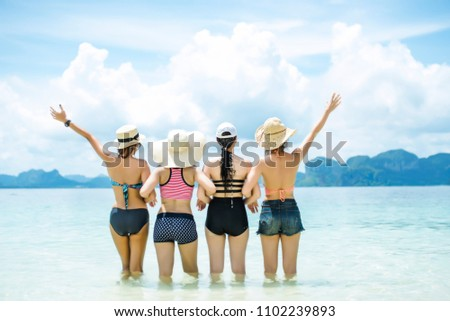 Group of happy friends wearing bikini , standing back side and open arms on the beach,enjoying summer vacation Summer concept and multiethnic friendship.
