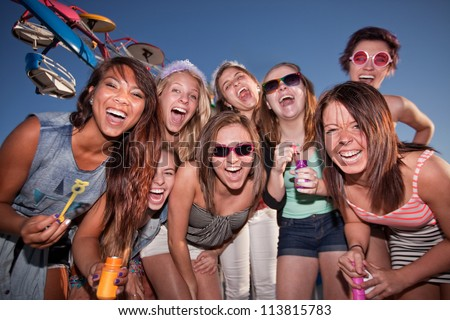 Group of happy girls with bubbles at amusement park - stock photo