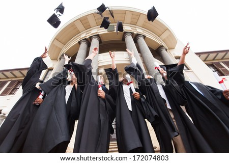 group of happy graduates throwing graduation hats in the air celebrating Stock photo ©