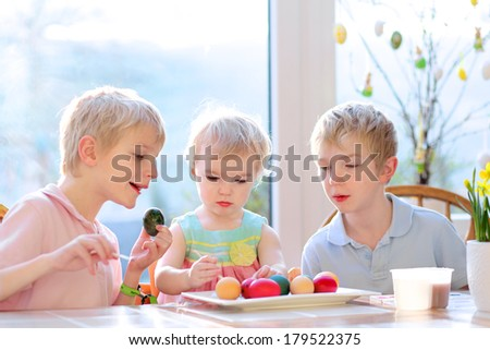 Group of happy kids from one family, two twin brothers and their little toddler sister, decorating and painting Easter eggs sitting together in the kitchen on a sunny day. Selective focus on girl. - stock photo