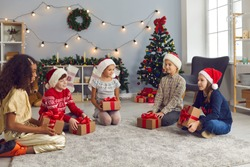 Group of happy kids in Santa hats trying to guess what's inside their gift boxes. Sisters and brother sitting on floor in cosy decorated living-room on Christmas morning, holding presents and talking