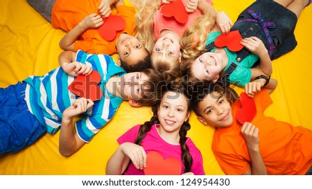 Group of happy kids laying in circle on the floor with hearts in their hands