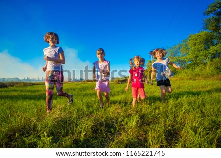 Group of happy kids running in green summer field #1165221745