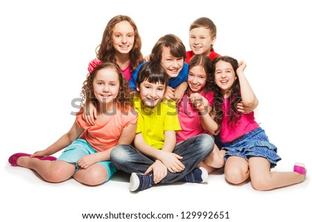 Group of happy kids sitting together hugging and smilng stock photo