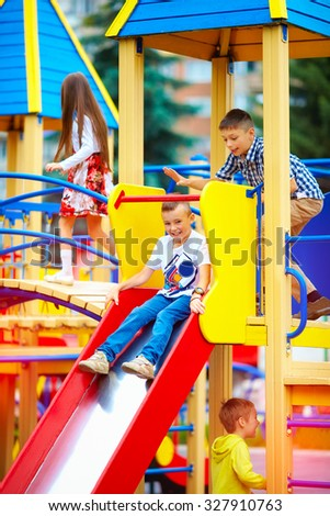 group of happy kids sliding on colorful playground