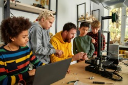 Group of happy kids with their male teacher looking at 3d printer and plastic detail prototype at robotics school lesson. Science and education. Inventions and creativity for kids
