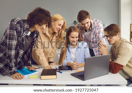 Group of happy male and female students looking at screen of modern laptop computer. School, university or college mates working on digital project together. Secondary and higher education concept Stock photo ©