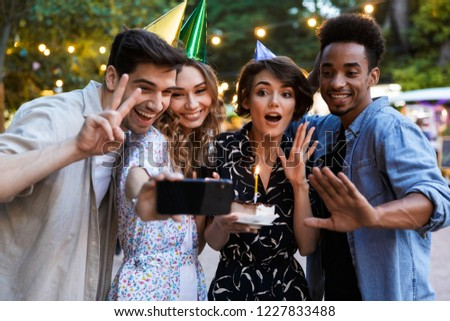 Group of happy multhiethnic friends celebrating with a cake outdoors, taking a selfie