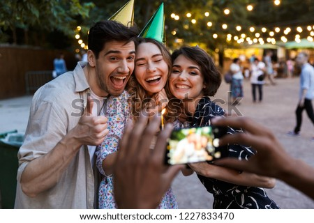 Group of happy multhiethnic friends celebrating with a cake outdoors, taking picture with photo camera