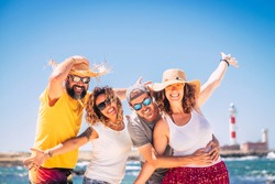 Group of happy people and cheerful adults friends have fun together during summer holiday vacation at the beach - enjoying the beach and ocean outdoor - blue sky and lighthouse in background