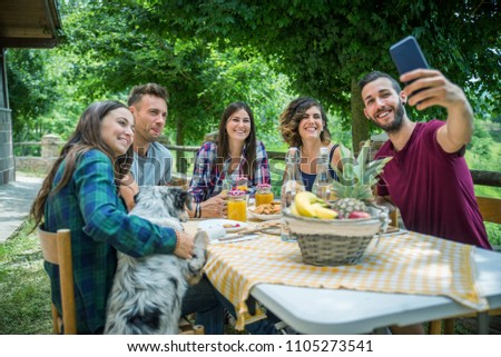 Group of happy people doing breakfast outdoors in a  traditional countryside - Friends eating snacks in the garden