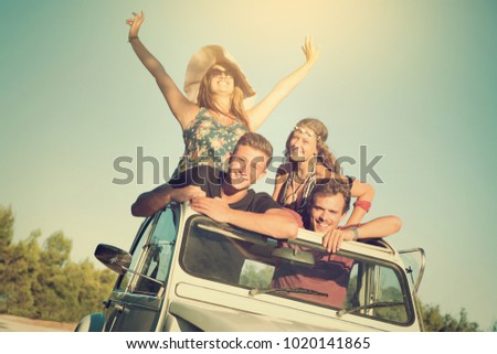 Group of happy people in a car at sunset in summer, ready for a roadtrip.