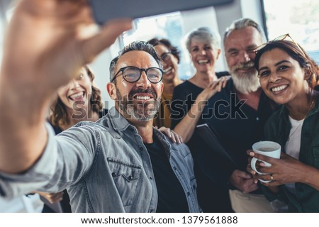 Group of happy people taking selfie in office. Start up entrepreneur at office taking selfie with his team.