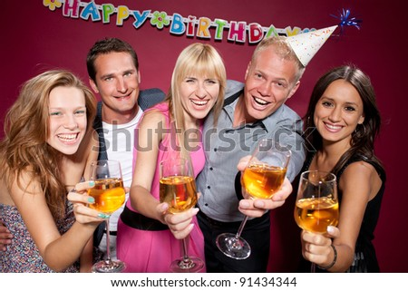 Group of happy people with wine glasses at birthday party