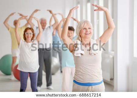Group of happy seniors during warm-up before exercise