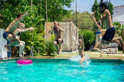 Group of happy six friends drinking jumping in pool day party with splash