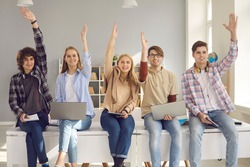 Group of happy smiling active students raising hands sitting on desk with digital devices. Young people agree with good idea or answer questions in lecture class. Studying at school or college concept