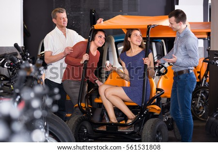 Group of happy smiling adult friends selecting grand tour electric at rental store. Selective focus