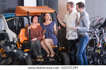 Group of happy smiling adult friends selecting grand tour electric for hire at rental