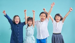 Group of happy smiling asian children hands up isolated on light blue background  .