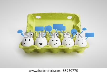 Group of happy smiling eggs with social chat sign and speech bubbles Ten white eggs in a carton box representing a social network On a gray background