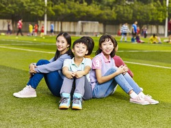 group of happy smiling elementary school boys and girls sitting on grass of playground.
