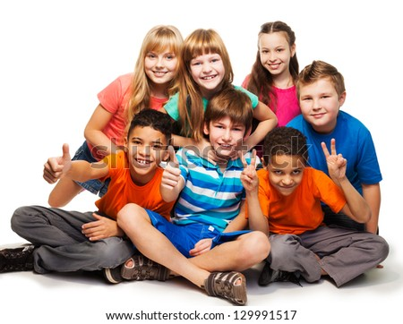 Group of happy smiling kids sitting together and playing - boys and girls black and Caucasian, isolated on white