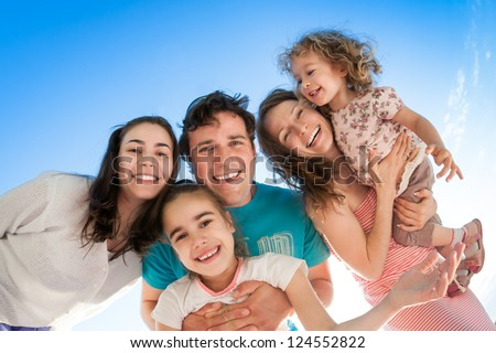 Group of happy smiling people against blue sky
