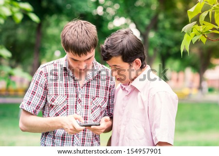 Group of happy smiling Teenage Students looking in tablet pc