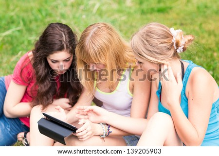 Group Of happy smiling Teenage Students outdoor Using Mobile Phone
