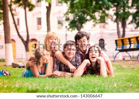 Group of happy smiling Teenage Students Outside lying on a grass