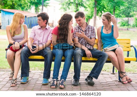 Group of happy smiling Teenage Students sitting on a banch