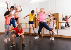 Group of happy sporty kids with female teacher training in modern dance studio, jumping together