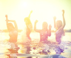 Group of happy teen girls playing in water at the beach on sunset. Beauty and joyful teenager friends having fun, dancing and spraying over summer sunset. Beach party. Sun flare.