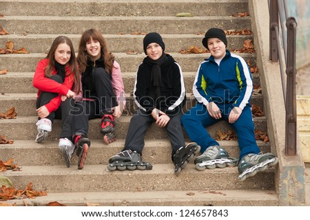 Group of happy teenagers in roller skates sitting on the stairs on beautiful autumn day.