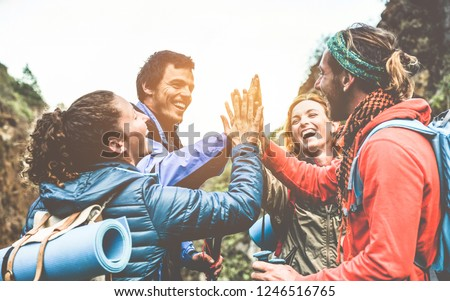 Group of happy trekkers stacking hands outdoor - Young hiker friends supporting each others - Survival, team, travel, success and adventure concept - Focus on hands