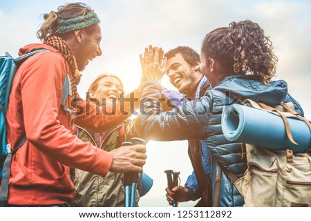 Group of happy trekkers stacking hands outdoor - Young hiker friends supporting each others - Survival, team, travel, success and adventure concept - Focus on hands #1253112892