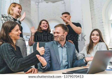 Group of happy young business people celebrating finishing successful project, congratulating their boss. Positive colleagues enjoying company income growth.