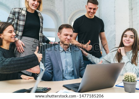 Group of happy young business people celebrating finishing successful project, congratulating their boss. Positive colleagues enjoying company income growth. Office life concept.