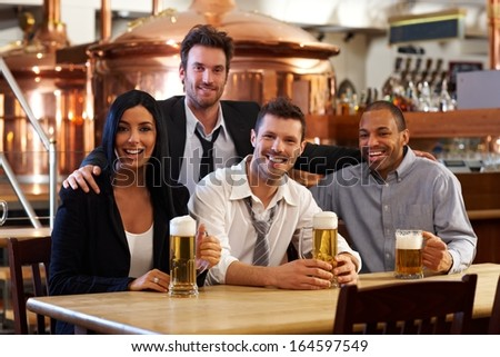 Group of happy young friends drinking beer at pub, smiling.