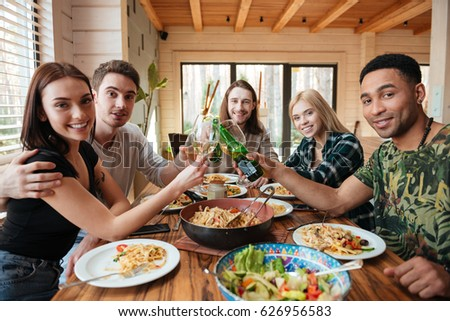 Group of happy young friends drinking wine and clinking glasses on the kitchen #626956583
