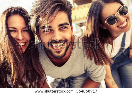 Group of happy young friends having fun on city street.Sunset.Close up image.
